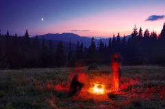 Camping in mountains. Evening in mountains and group of tourists make a supper on a fire near tent Stock Photos