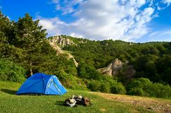 Camping in the mountains. Blue tent on grassy field with mountains and trees in the background, blue sky and clouds Stock Photo