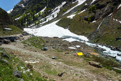 Camping in the mountains. A bright yellow camp in the mountains near a glacier of pure white snow in Jammu and Kashmir, India. It is a popular destination for Royalty Free Stock Photo