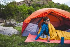 Camping in the mountains. Camping in the forest. A girl is preparing coffee on a geyser coffee machine. A woman sits near a tent in a sleeping bag and prepares royalty free stock image