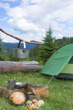 Camping in the mountains and cooking food from mushrooms. Hiking in the mountains in the summer with the collection of mushrooms Royalty Free Stock Photo