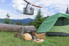 Camping in the mountains and cooking food from mushrooms. Hiking in the mountains in the summer with the collection of mushrooms Stock Image