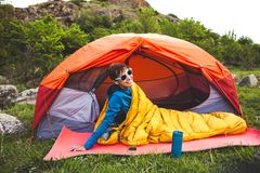 Camping in the mountains. Camping in the forest. A girl is preparing coffee on a geyser coffee machine. A woman sits near a tent in a sleeping bag and prepares royalty free stock photo