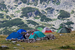 Camping in the Mountains. Hikinig in the Retezat mountains, Romania. Tents and camping equipment high up in the mountains in a rocky area Stock Images
