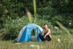 Camping in the mountains. A man sits near tent against the backdrop of green trees and mountains. Royalty Free Stock Photo