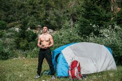 Camping in the mountains. A man stand near tent against the back Stock Image