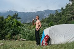 Camping in the mountains. A man stand near tent against the backdrop of green trees and mountains. Royalty Free Stock Photography