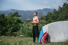 Camping in the mountains. A man stand near tent against the backdrop of green trees and mountains. Stock Photos