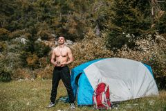Camping in the mountains. A man stand near tent against the backdrop of green trees and mountains. Royalty Free Stock Photos