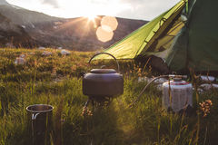 Camping in the mountains at morning. Camping teapot and cap on the gras at sunrise time. Mountains of Bulgaria Stock Image