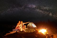 Tourist family with daughter having a rest in mountains at night under starry sky with Milky way. Camping in mountains at night. Tourist family resting in front Royalty Free Stock Photography
