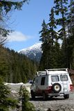 Camping in the Mountains. Red and white camper van with the mountains off in the background Stock Photos