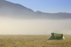 Camping in mountains. Tent in mountains in a fog morning Royalty Free Stock Photo