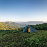 Camping in mountains. Tent in mountains at sunrise Royalty Free Stock Photo
