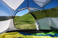 Camping in the mountains. View from tent entrance on beautiful lake in the morning. Camping in the mountains royalty free stock images