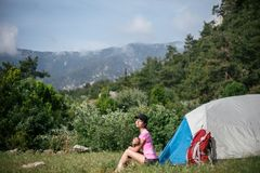 Camping in the mountains. A woman sits near tent against the backdrop of green trees and mountains. Royalty Free Stock Images