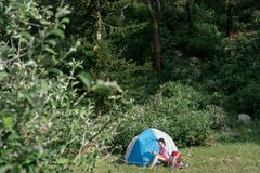 Camping in the mountains. A woman sits near tent against the backdrop of green trees and mountains. Royalty Free Stock Photo