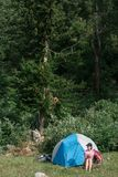 Camping in the mountains. A woman sits near tent against the backdrop of green trees and mountains. Stock Photos