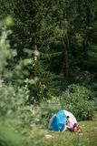 Camping in the mountains. A woman sits near tent against the backdrop of green trees and mountains. Royalty Free Stock Photography