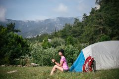 Camping in the mountains. A woman sits near tent against the backdrop of green trees and mountains. Stock Images