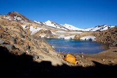 Camping in the mountains. Yellow tent in a camp at a mountain lake Royalty Free Stock Photography