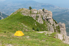 Camping in the mountains. Yellow tent on green meadow in the mountains Stock Images