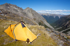 Camping in the mountains. Yellow tent pitched above mountain valley Royalty Free Stock Images