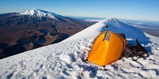 Camping in the mountains. Yellow tent pitched at the top of volcano Stock Photography