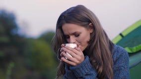 camping Mujer turística que bebe la bebida caliente en naturaleza metrajes