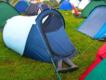 Camping at music festival tents and wellington boots. A pair of wellington boots protrude from the entrance of a tent on a campsite at a summer music festival in Stock Image