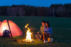 Camping night couple cook by campfire romantic. Camping night couple cook by campfire backpack in romantic countryside Stock Image