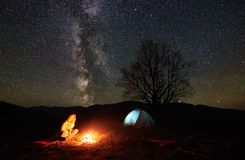 Night camping in mountains. Female hiker resting near campfire, tourist tent under starry sky stock images
