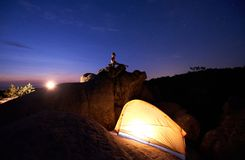 Camping at night on rock formation. Tourist tent and woman doing yoga on mountain top stock photo