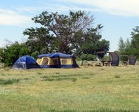 Camp tents and picnic tables. Camping out in tents at campground near lake in Colorado stock photography
