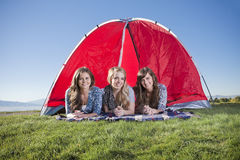 Camping in the outdoors. A wide angle photo of three attractive women enjoying a day camping in the outdoors Stock Image