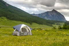 Camping Outdoors in the Mountains of Colorado. Small camping tent with chairs setup in mountain meadow filled with wildflowers with high mountain peak in Stock Photo