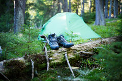 Camping people putting on hiking shoes by tent Royalty Free Stock Photos