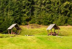 Camping place on a glade in forest. Lovely leisure scenery with two empty gazebos Royalty Free Stock Image