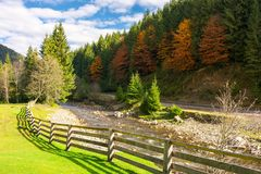 Camping place near the river. Wooden fence on a grassy lawn along the shore. road under the hill with trees in fall color. beautiful sunny autumn weather stock photo