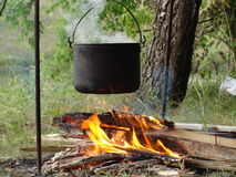 Camping pot and campfire. Closeup of the retro dixy steaming on the campfire Royalty Free Stock Images