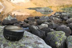 Camping pot with water in the background of mountains mirror reflection in the lake. Hiking motivational image royalty free stock photography