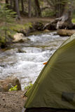 Camping Beside A River. A generic tent campsite next to a rushing river. Perfect to illustrate roughing it in nature royalty free stock image