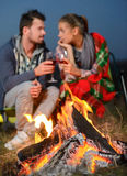 Camping. Romantic evening. Charming couple near a fire while camping drinking wine stock image