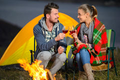 Camping. Romantic evening. Charming couple near a fire while camping drinking wine royalty free stock photography