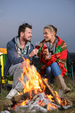 Camping. Romantic evening. Charming couple near a fire while camping drinking wine stock photo