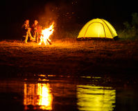 Camping. Romantic evening. A charming couple, camping, sitting around the campfire Royalty Free Stock Photo