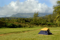 Camping in Scenic Kauai. A lone tent sits on a grassy field with the Kauai Mountains in the background.  Tent is a dome tent, yellow and navy blue Royalty Free Stock Photography