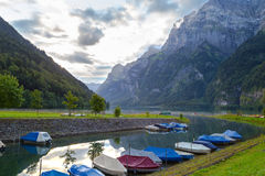 Camping on the shore of the lake. Boats on the dock. Switzerlan. Foggy morning in the Swiss Alps. Mountain lake Klontalersee on  background of majestic mountains Stock Images