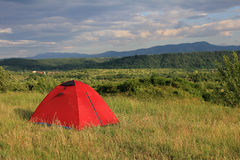 Camping site. Red tent in a camping site between hills Stock Image