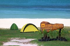 Camping site on the beach with tents and ocean background Royalty Free Stock Photo